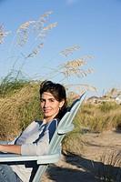 Woman sitting in chair at beach