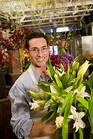 A man stands in a florist and holds flowers