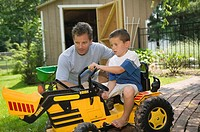 Father helping son drive toy tractor