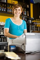 Smiling woman standing behind cash register