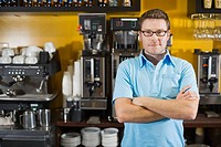 Hipster man standing beside espresso machine