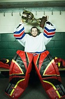 Ice hockey goaltender holding up trophy