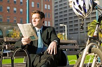 Businessman reading newspaper on park bench