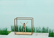 Young woman standing inside square structure with arms raised, facing body of water