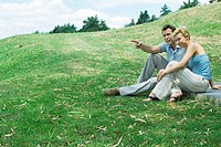 Couple sitting on grassy hill together