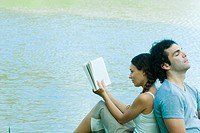 Couple sitting back to back next to water, woman reading