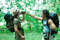 Two hikers, one holding water bottle for other