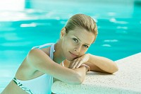 Young woman in pool, leaning against edge of pool (thumbnail)