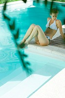 Young woman sitting by pool, full length (thumbnail)