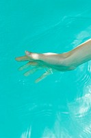 Young woman dipping hand into water, close-up