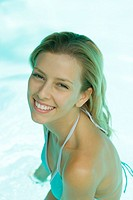 Young woman in pool, smiling at camera, portrait