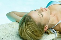 Young woman lying by edge of pool, eyes closed