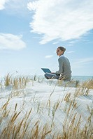 Woman sitting on dune, using laptop
