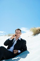 Businessman sitting on dune, using cell phone