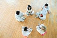 Group therapy, adults sitting on floor in circle