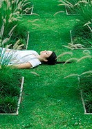 Woman lying on grass, eyes closed