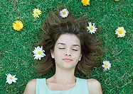 Woman lying on grass with flowers scattered around head, eyes closed