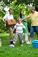 Boy 6-8 kicking ball in park with family carrying picnic things