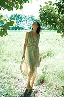 Young woman wearing sundress and holding sun hat, standing looking up at trees