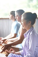 Three people meditating in yoga class, side view focus on woman