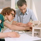 Woman and man working with architectural model