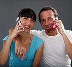 Young woman and mature man, using mobile phones, smiling, portrait