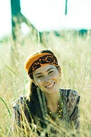 Young woman wearing scarf around head, in field, portrait