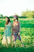 Young hippie women standing in field, looking away, full length