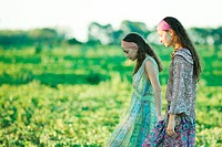 Young hippie women walking through field, side view