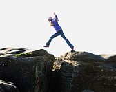 Girl 7-9 jumping between rocks, side view, blurred motion