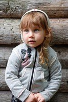 Girl 2-4 wearing hooded top, beside wooden cabin