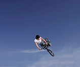 Young man performing stunt on bike against blue sky