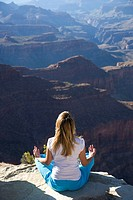 USA, Arizona, Grand Canyon National Park, woman in lotus position on cliff edge, rear view