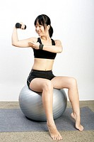 Young woman sitting on exercise ball pointing to muscle in gym
