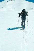 Skier heading toward mountain, rear view