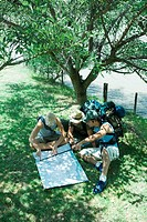 Hikers sitting on ground, looking at map