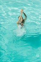 Young woman standing in pool, splashing with arms over head, full length, high angle view