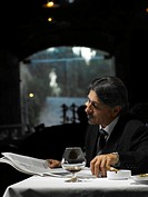 Senior businessman reading newspaper in restaurant