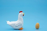 Clay model of chicken and egg on blue background