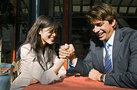 Young businessman and businesswoman sitting at table, arm wrestling, laughing
