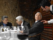 Waiter talking to businessman in restaurant with colleagues