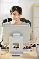 Mature businesswoman using computer, smiling, portrait