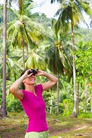 Woman looking through binoculars in forest