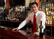Bartender behind bar counter in pub, portrait