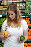 Woman holding yellow and red peppers in supermarket