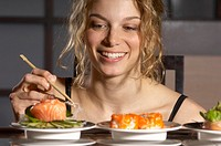 Young woman holding chopsticks with sushi