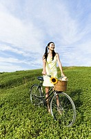 Woman on hill with bicycle looking to side