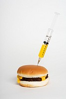 Hypodermic needle injecting yellow liquid into cheeseburger