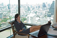 Businesswoman using mobile phone in office, feet up, side view