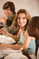 Woman sitting at dinner table with friends